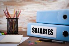 Lön kontorslimbindning på träskrivbordet På tabellen färgad penna Royaltyfri Foto