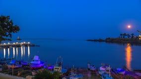 Löneförhöjning av månen över fjärden av staden Ahtopol med en hamn för fiskebåtar, pir och fyr lökformig royaltyfri bild