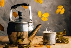 Lönnlöv och varmt te i en teservis skapar ett höstlynne Fallande sidor och färgstänk av mjölkar te cozy arkivfoto