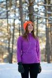 Löpare för ung kvinna som ler och ser upp i härlig vinterskog på Sunny Frosty Day Aktiv livsstil och sport Royaltyfria Bilder