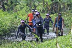 Löpare har roliga korsa Muddy Tracks Arkivbild