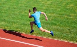 Löpare som fångas i midair Kort avståndsspringutmaning Ökningshastighet Bakgrund för gräs för idrottsman nenkörningsspår Kör in i arkivbild
