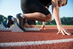 Löpare som förbereder sig för lopp på startgrop arkivfoto