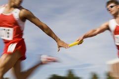 Löpare som passerar taktpinnen i stafett Fotografering för Bildbyråer