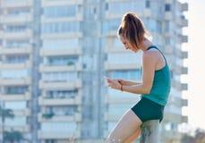 Löpareflicka som har en vila och använder smartphonen Fotografering för Bildbyråer