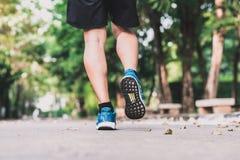 Löparefoten som joggar i morgon på, parkerar Fotografering för Bildbyråer