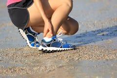 Löparehållen hennes sportar sårade ankeln under sportar som utbildar på stranden Royaltyfria Foton