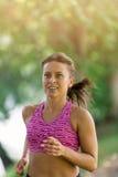 Löpareidrottsman nenspring på parkerar begrepp för wellness för genomkörare för kvinnakondition jogga royaltyfri foto