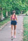 Löpareidrottsman nenspring på parkerar begrepp för wellness för genomkörare för kvinnakondition jogga arkivfoto