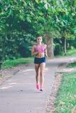 Löpareidrottsman nenspring på parkerar begrepp för wellness för genomkörare för kvinnakondition jogga royaltyfri bild