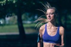 Löpareidrottsman nenspring på parkerar begrepp för wellness för genomkörare för kvinnakondition jogga royaltyfria bilder