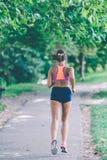 Löpareidrottsman nenspring på parkerar begrepp för wellness för genomkörare för kvinnakondition jogga arkivbilder
