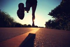 Löpareidrottsman nenspring på sjösidavägen royaltyfri fotografi