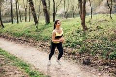 Löpareidrottsman nenspring på tropiskt parkerar begrepp för wellness för genomkörare för kvinnakondition jogga fotografering för bildbyråer