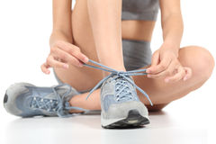 Löparekonditionkvinna som binder skosnören som är klara till sporten arkivbild