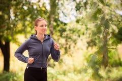 Löparekvinna som joggar i den utomhus- naturen Fotografering för Bildbyråer