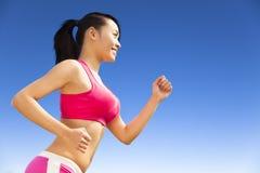 Löparekvinna som joggar i solig dag Royaltyfri Fotografi