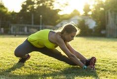 Löparekvinna som sträcker i stadion som utomhus övar wearable teknologi för konditionbogserare Fotografering för Bildbyråer