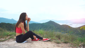 Löparekvinnan äter äpplet på bergmaximum royaltyfri foto