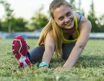 Löparekvinnan sträckte i stadion som utomhus övar wearable teknologi för konditionbogserare Fotografering för Bildbyråer