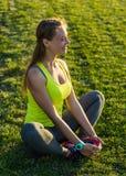 Löparekvinnan sträckte i stadion som utomhus övar wearable teknologi för konditionbogserare Royaltyfri Bild