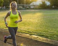 Löparekvinnaspring i stadion som utomhus övar wearable teknologi för konditionbogserare Fotografering för Bildbyråer