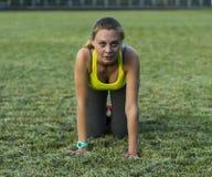 Löparekvinnaspring i stadion som utomhus övar wearable teknologi för konditionbogserare Royaltyfri Bild