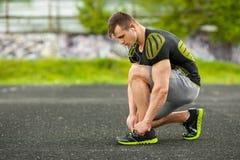 Löpareman som binder skosnöret i stadion, genomkörare för arg utbildning Sportig manlig utbildning utanför royaltyfri fotografi