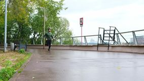 Löparemannen som kör på, parkerar banan som övar på att regna dag Färdig manlig konditionmodellutbildning som gör fritids- jogga arkivfilmer