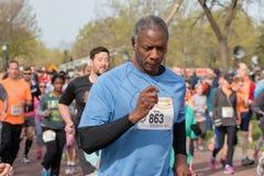 Löparen konkurrerar i halv maraton för vår Arkivfoton