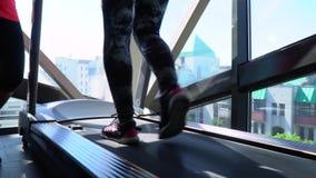 Löparen utbildar inomhus Flickan mot bakgrunden av ett stort fönster går på en löparbana stock video