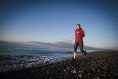 Löparespring för vuxen kvinna på soluppgångsjösidan Sund livsstil royaltyfria foton