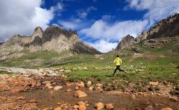 Löparespring på berg för hög höjd arkivbild