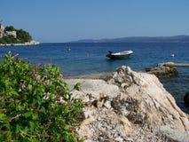 Lös stenig strand i Kroatien med ett litet fartyg Arkivbild