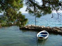 Lös stenig strand i Kroatien med ett litet fartyg Fotografering för Bildbyråer