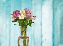Lösa blommor i vas på blå wood bakgrund Arkivbilder