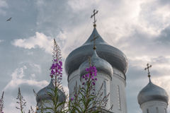 Lösa blommor mot kristna kors Royaltyfri Bild