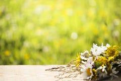Lösa blommor på det wood tabellperspektivet och suddig bakgrund för gräsplanbokeh Arkivfoton
