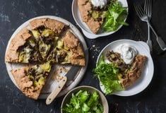 Lösa champinjoner, potatisar, mozzarella, hel korngalette med grekisk yoghurt och grön sallad på en mörk bakgrund, bästa sikt Arkivbilder