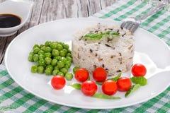 Lösa och bruna organiska ris med körsbärsröda tomater, gröna ärtor Royaltyfri Fotografi