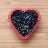 Lösa ris i en hjärtaformbunke Royaltyfri Bild
