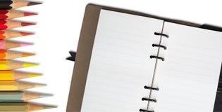 Löschen Sie offenes Anmerkungs-Buch und heiße Tone Color Pencil lizenzfreie stockfotos