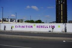 Löschungs-Aufstandsnamen- und -logospray gemalt auf Horten der Baustelle stockbild