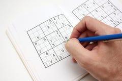 Lösen eines SUDOKU-Puzzlespiels Lizenzfreie Stockfotografie