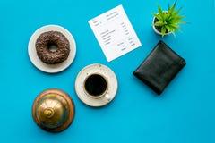 Lösen Sie den Wechsel, Lohn am Restaurant ein Kontrolle nahe Geldbörse, Service-Glocke, Kaffee auf Draufsicht des blauen Hintergr stockfotos