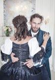 Lösendes Korsett des gutaussehenden Mannes der Frau im mittelalterlichen Kleid lizenzfreies stockfoto