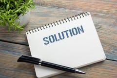 lösning Notepad med meddelandet, pennan och blomman Kontorstillförsel på bästa sikt för skrivbordtabell Fotografering för Bildbyråer