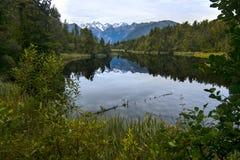 Löst naturlandskap med olik vegetation och den fridsamma sjön av ursprungligt klart vatten med bergspegelreflexion, Nya Zeeland arkivfoto