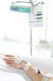 Lösung IV in einer geduldigen Hand mit IV Maschine lizenzfreie stockbilder