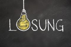 `Lösung` text with an idea light bulb on chalk board. Translation: `Solution` stock illustration